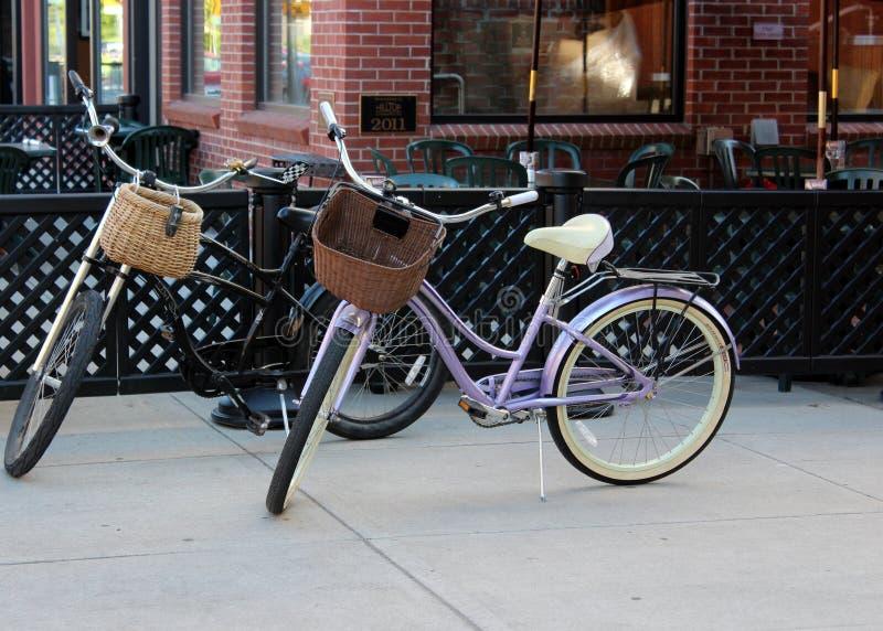 Zwei altmodische Fahrräder mit Strohkörben auf den Lenkstangen, dargelegt, damit Leute auf Bürgersteig vor Geschäft, eine leichte stockfoto