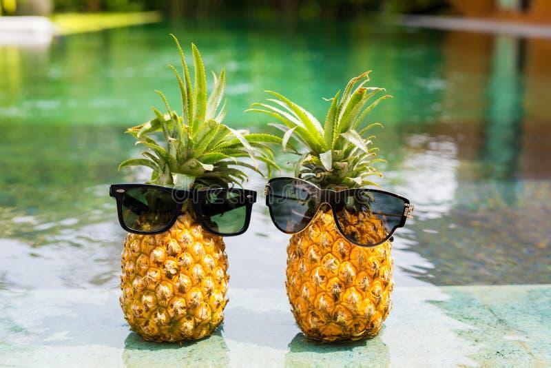 Zwei Ananas mit der Sonnenbrille, die durch das Pool kühlt stockfotografie