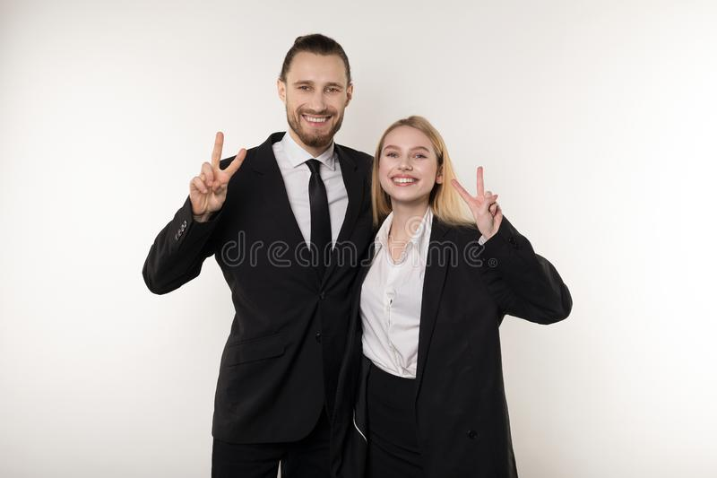 Zwei Angestellte lachen glücklich über das Ende der Arbeitswoche, zeigen viktory Zeichen und betrachten die Kamera stockfotos