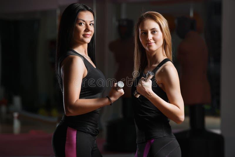 Zwei anhebende Dummköpfe des jungen schönen sportlichen Mädchens in der Turnhalle lizenzfreie stockbilder