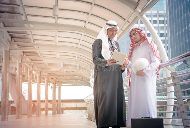 Zwei arabische Geschäftsleute, die sich zusammen besprechen stockfotografie