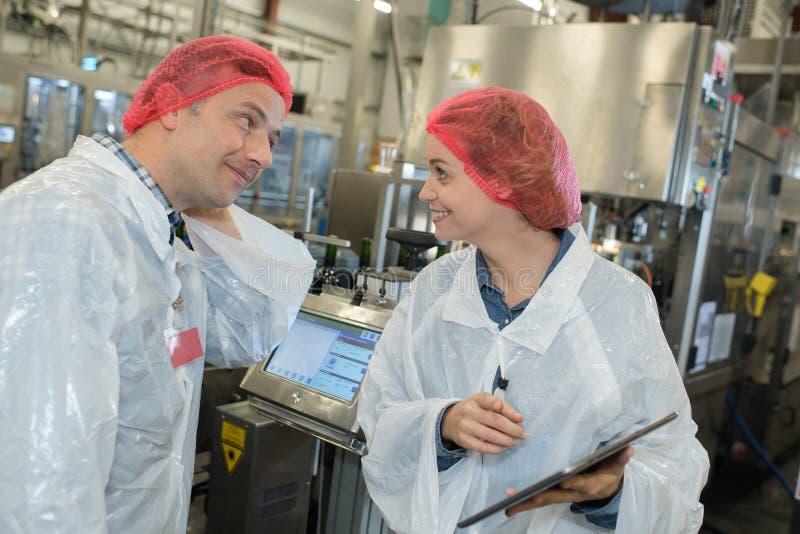 Zwei Arbeiter, die in der Fabrik sprechen lizenzfreies stockfoto