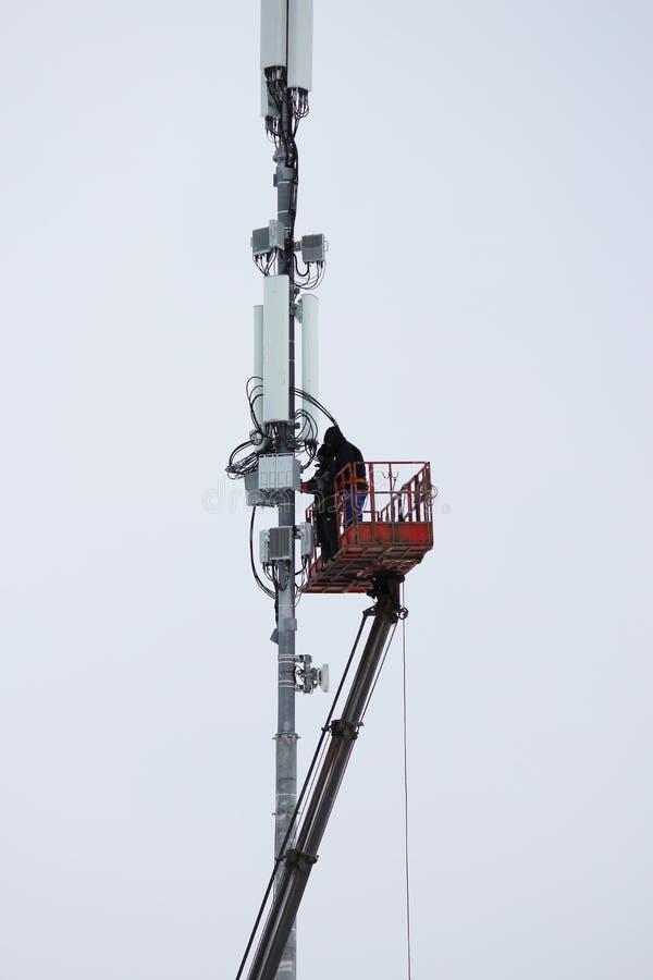 Zwei Arbeitskräfte bauen Ausrüstung für Telekommunikation auf dem Turm mithilfe des Aufzugs im Winter zusammen lizenzfreies stockfoto