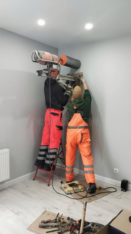 Zwei Arbeitskräfte bohren ein Loch in der Wand, Diamantbohrung Vorbereitung für Installation von Wärmetauschern - Wärmeaustausche lizenzfreies stockfoto