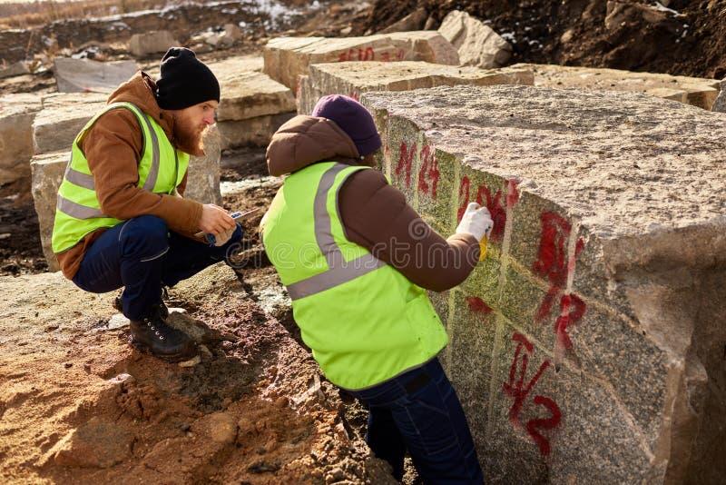 Zwei Arbeitskräfte, die Granit-Blöcke markieren lizenzfreies stockfoto