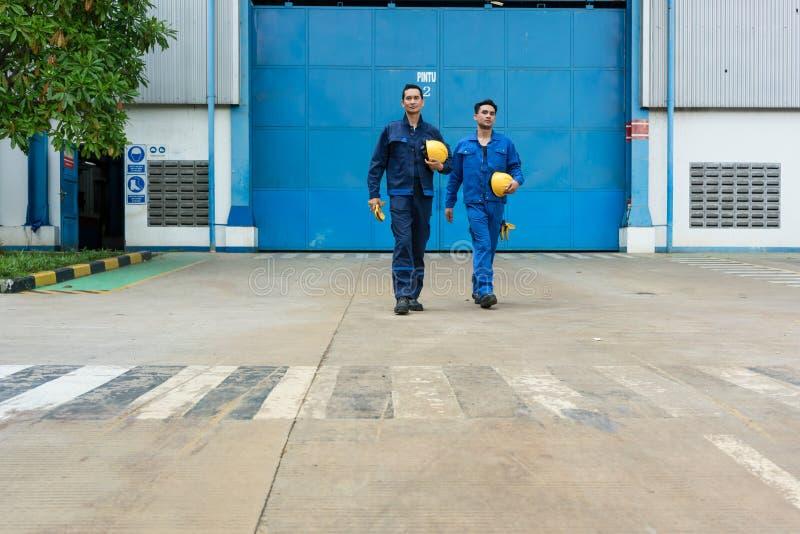 Zwei Arbeitskräfte, die heraus nach der Arbeit von der Fabrik gehen stockbild
