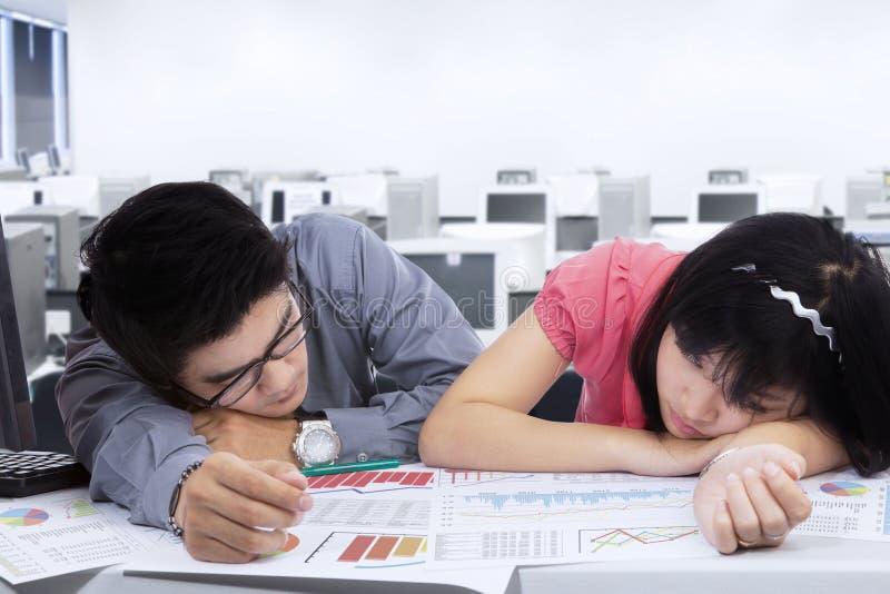 Zwei Arbeitskräfte schauen im Büro schläfrig stockbild