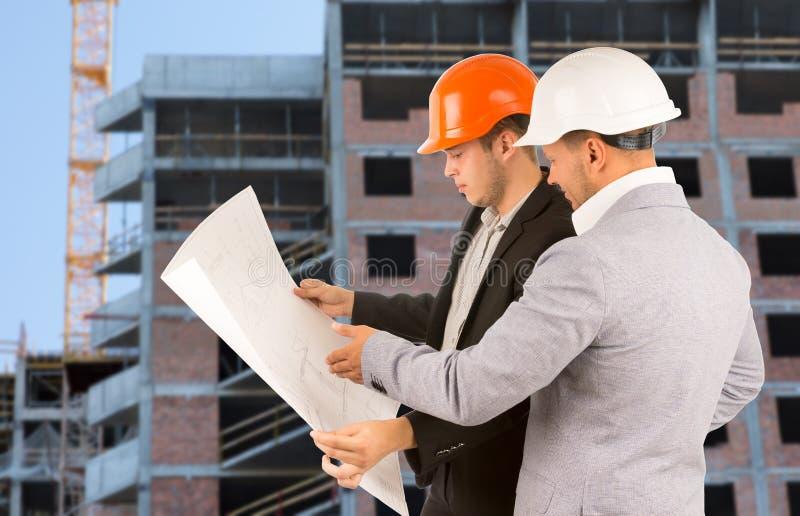 Zwei Architekten, die einen Gebäudeplan besprechen stockfoto