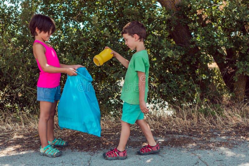 Zwei Artenkinder, die Schulaufgaben tun und Abfall mit einer Plastiktasche im Park sammeln stockbild