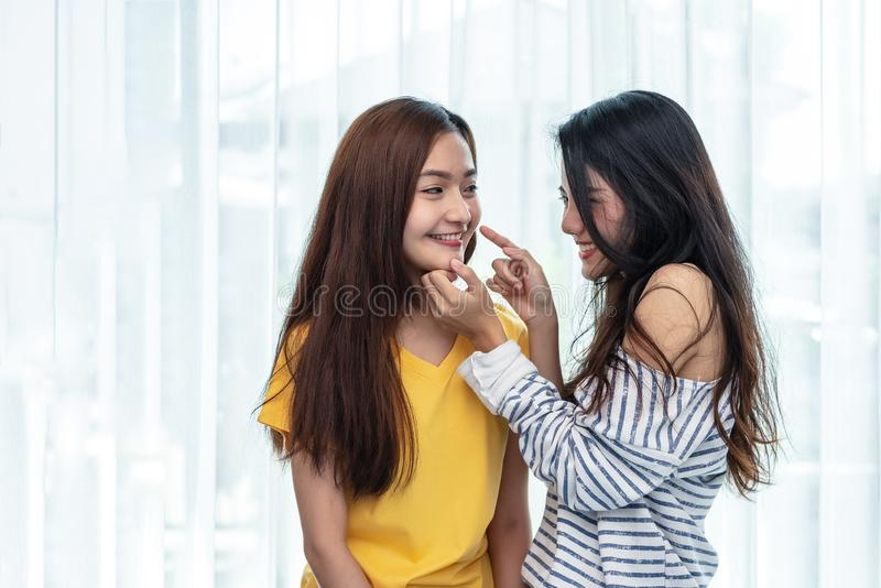 Zwei Asiatinnen, die Kinn ber?hren und mit zusammen spielen Leute und Lebensstilkonzept LGBT-Stolzthema lizenzfreies stockfoto
