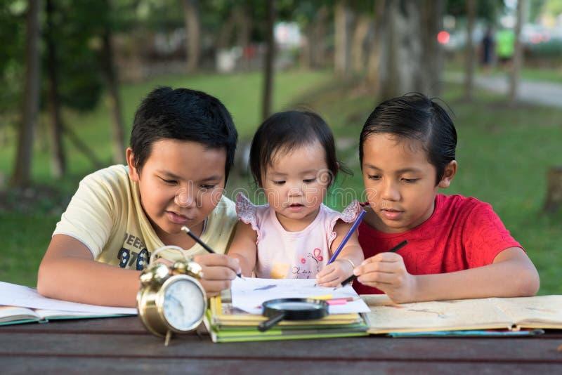 Zwei asiatische Brüder, die mit ihrer kleinen Schwester zusammen zeichnet spielen stockbild