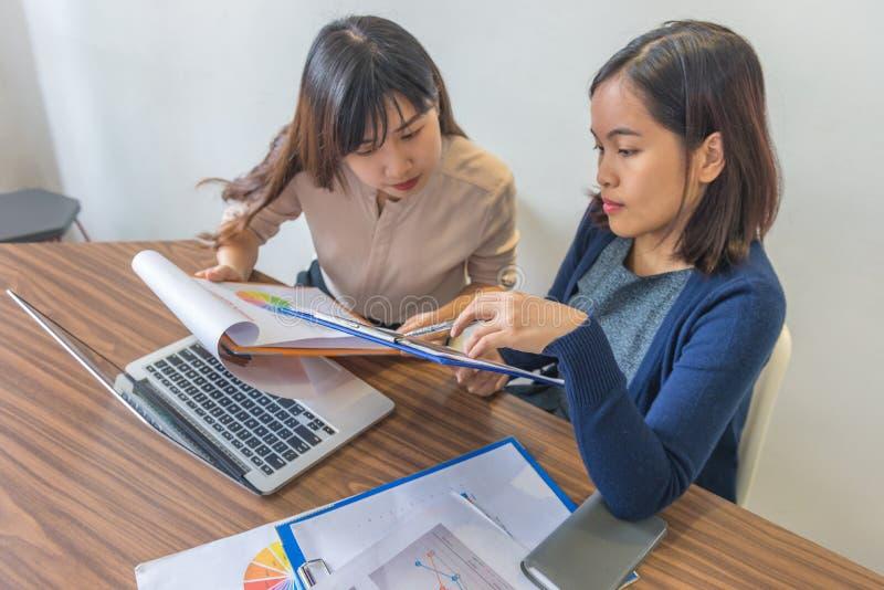 Zwei asiatische Buchhalterinnen arbeiten zusammen an einem Finanzbericht-Dokument lizenzfreies stockfoto