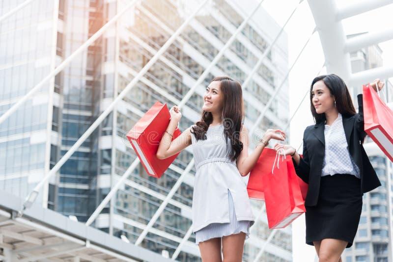 Zwei asiatische Geschäftsfrauen, die rote Einkaufstaschen mit Kaufhaushintergrund in der Metropole oder in der Stadt tragen Entsp lizenzfreie stockbilder
