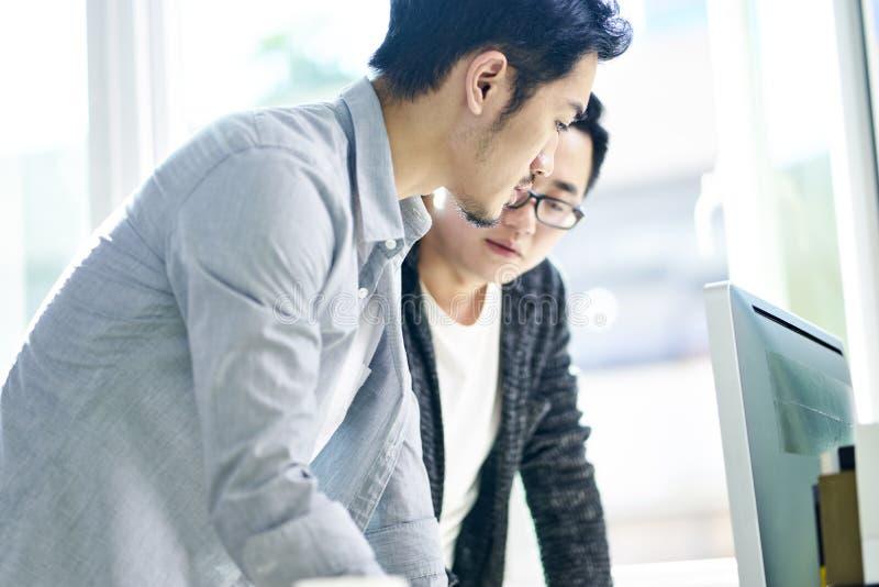 Zwei asiatische Geschäftsleute, die im Büro zusammenarbeiten stockfotos