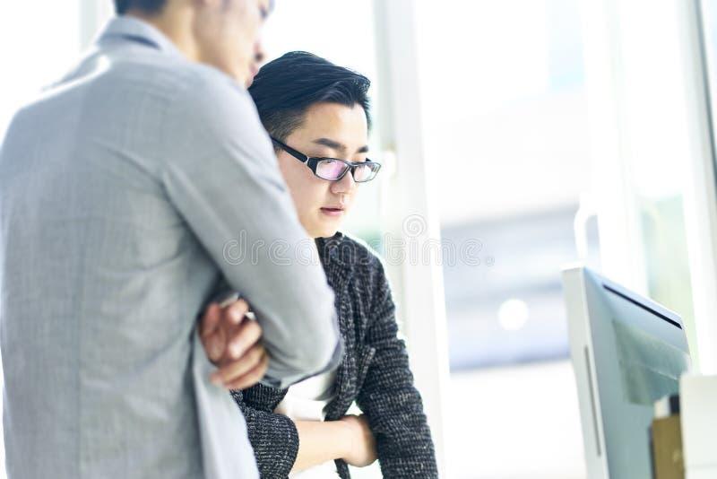 Zwei asiatische Geschäftsleute, die im Büro zusammenarbeiten lizenzfreies stockbild