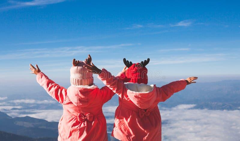 Zwei asiatische Kindermädchen, die Strickjacke und warmen Hut tragen, heben ihre Arme an, die den schönen Nebel und den Berg mit  stockbild