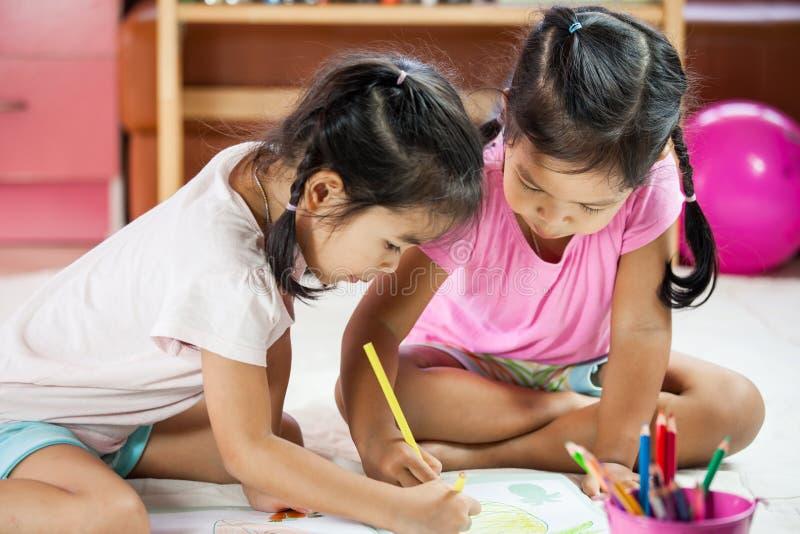 Zwei asiatische kleine Mädchen, die mit Zeichenstift zu malen den Spaß, haben stockfoto