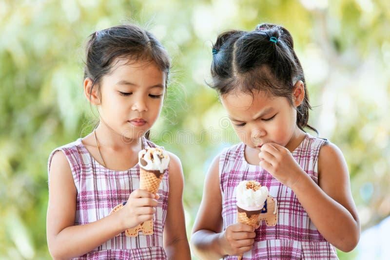 Zwei asiatische kleines Kindermädchen, die köstlichen Eiscremekegel essen stockbilder