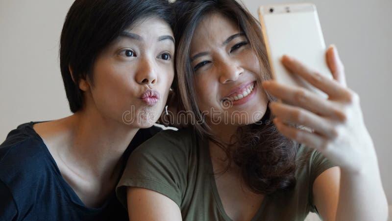 Zwei asiatische Mädchen der Mischrasse, die selfie mit intelligentem Telefon nehmen stockbilder