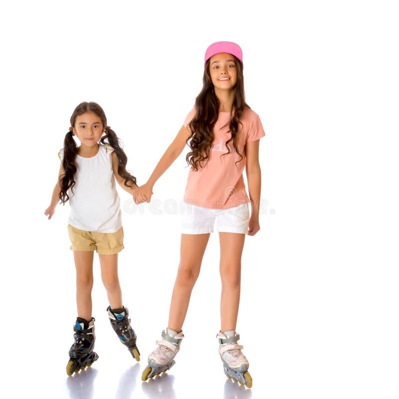 Zwei asiatische Mädchen laufen Rollschuh lizenzfreie stockbilder