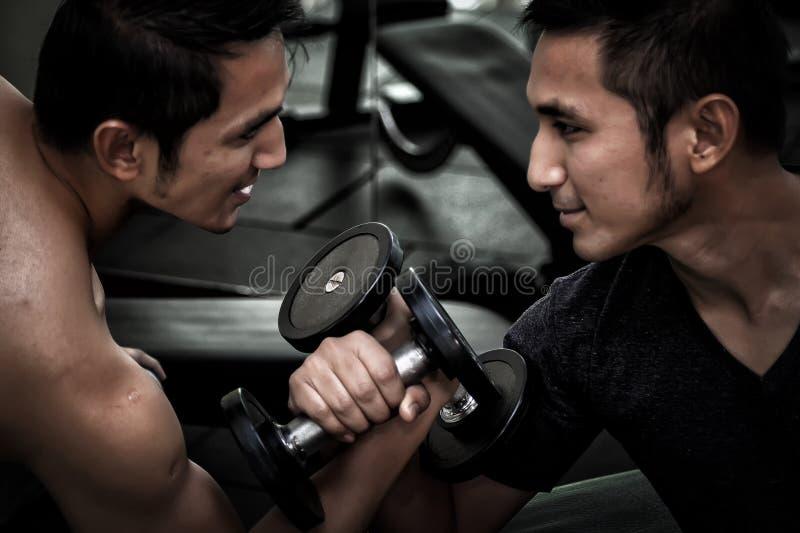 Zwei asiatische Männer verwenden Dummkopfübungs-Gewichthebenarmwringen c stockfoto