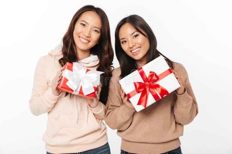Zwei asiatische nette Damenschwestern, die Geschenkboxüberraschung halten stockbild