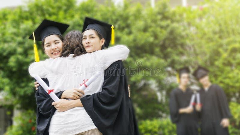 Zwei asiatische Studentinnen mit den Staffelungskleidern und -hut umarmen Th stockbilder