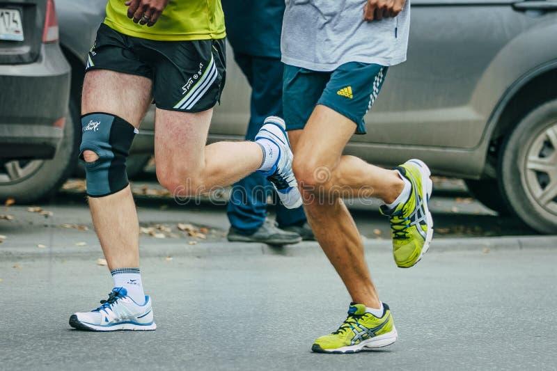Zwei Athleten, die entlang eine Straße in der Stadt laufen lizenzfreie stockfotografie