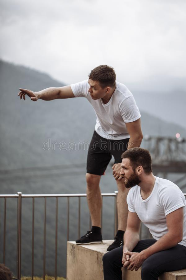 Zwei Athleten stehen nach intensivem Trainingstraining im Freien in der Berglandschaft still lizenzfreies stockfoto