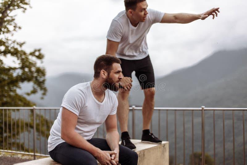 Zwei Athleten stehen nach intensivem Trainingstraining im Freien in der Berglandschaft still stockfotos