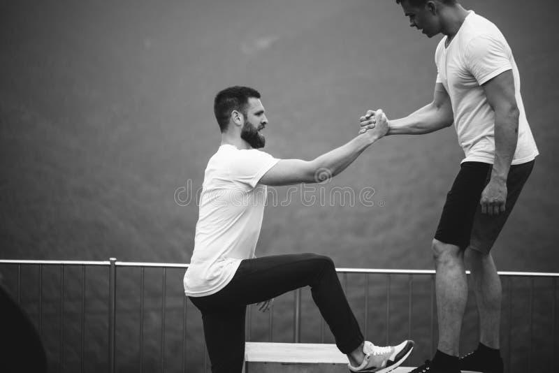 Zwei Athleten stehen nach intensivem Trainingstraining im Freien in der Berglandschaft still stockbilder