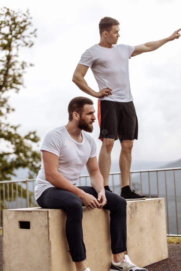 Zwei Athleten stehen nach intensivem Trainingstraining im Freien in der Berglandschaft still lizenzfreie stockbilder