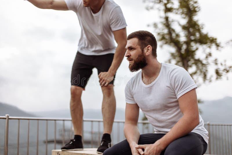 Zwei Athleten stehen nach intensivem Trainingstraining im Freien in der Berglandschaft still lizenzfreie stockfotos