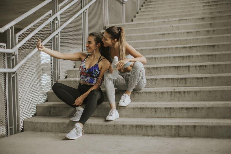 Zwei Athletenfrauen, die selfie nachdem dem Rütteln stillstehen und nehmen stockfoto