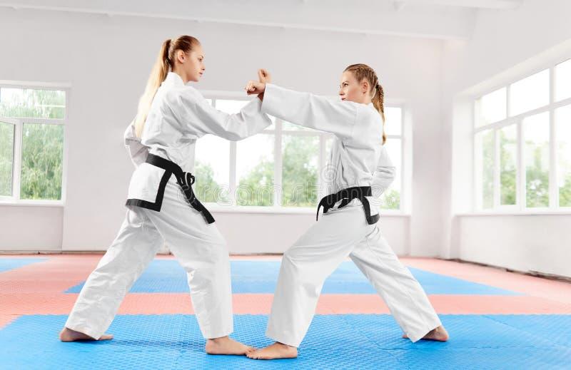 Zwei athletische Mädchen, die unter Verwendung der Karatetechniken im hellen Karate kämpfen, klassifizieren stockfotos