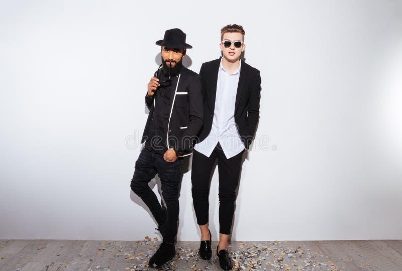 Zwei attraktive überzeugte junge Männer in den modernen schwarzen Anzügen lizenzfreie stockfotos