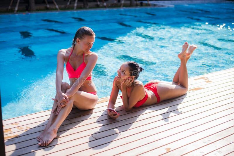 Zwei attraktive blonde und Brunettemädchen mit dem langen Haar liegen auf Flor nahe Pool Sie tragen Bikini und Badeanzug sie lizenzfreies stockbild