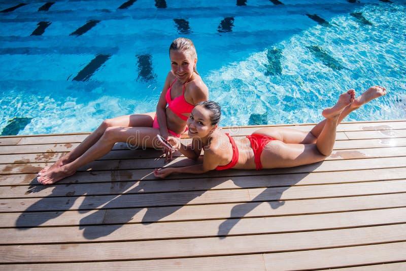Zwei attraktive blonde und Brunettemädchen mit dem langen Haar liegen auf Flor nahe Pool Sie tragen Bikini und Badeanzug sie lizenzfreies stockfoto