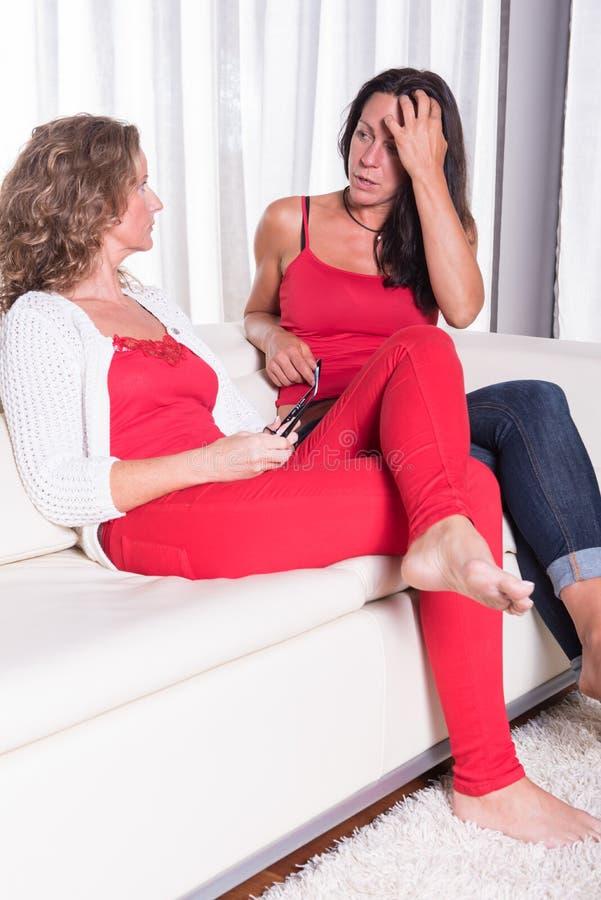 Zwei attraktive Frauen, die auf der Couch und der Unterhaltung sitiing sind stockbilder
