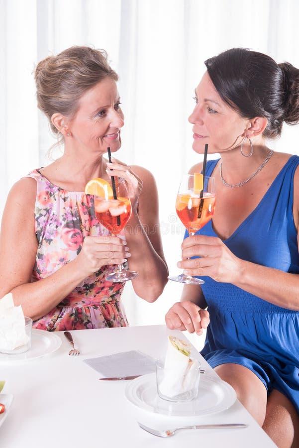 Zwei attraktive Frauen, die helles zu Abend essen stockbilder