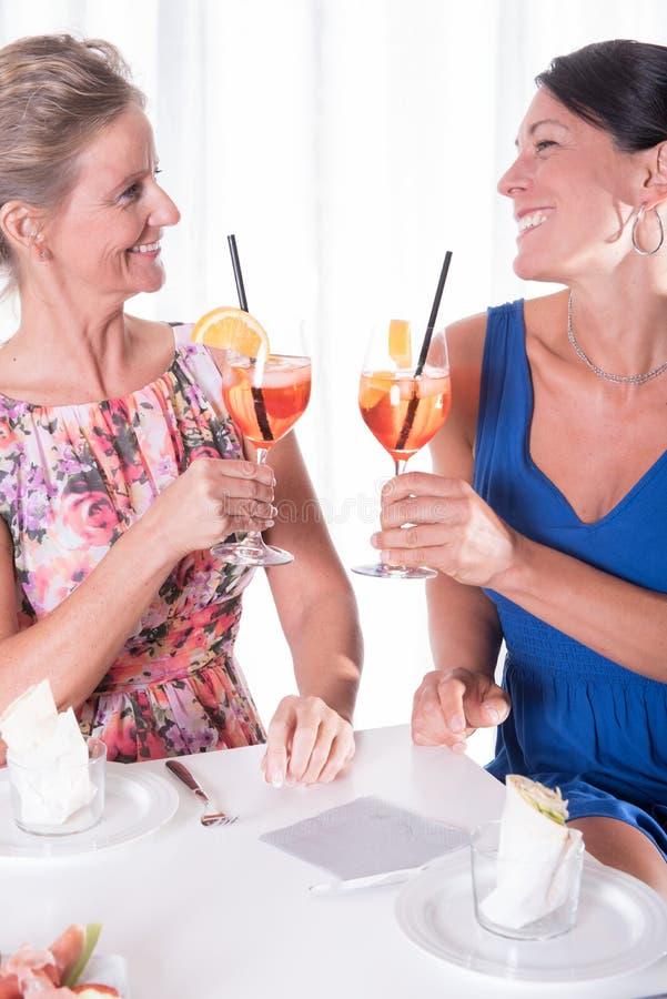 Zwei attraktive Frauen, die helles zu Abend essen stockfotografie