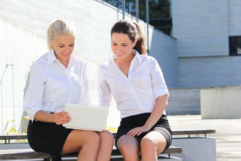 Zwei attraktive Geschäftsfrauen, die mit Laptop über Straßenba sitzen stockbilder