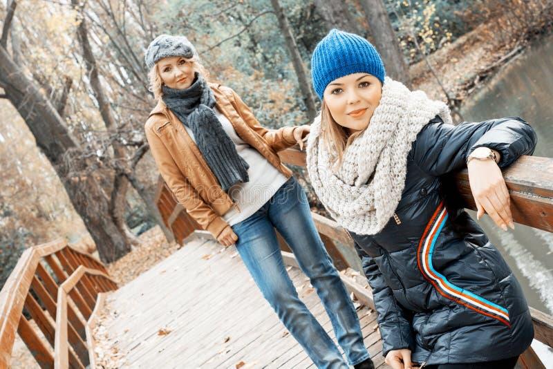 Zwei attraktive junge Frauen, die auf einer Brücke aufwerfen lizenzfreie stockfotografie