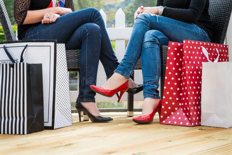 Zwei attraktive junge Freundinnen, die einen Bruch nach dem erfolgreichen Einkaufen genießen lizenzfreies stockbild