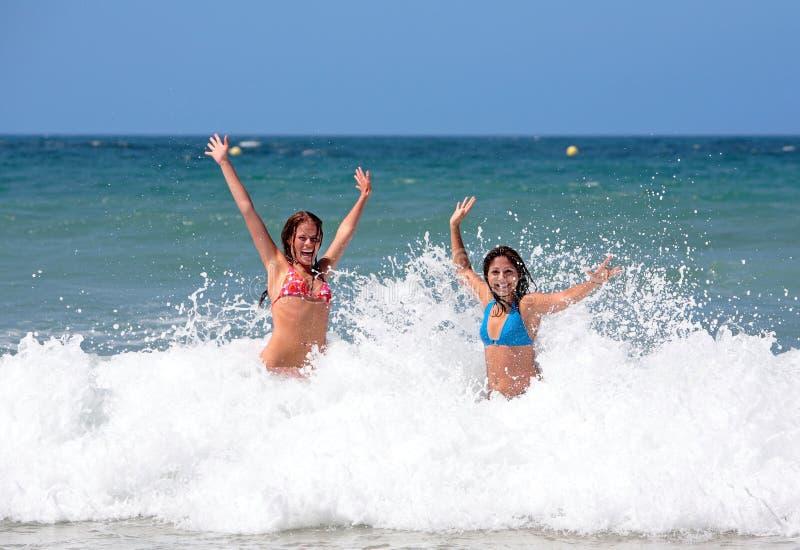 Zwei attraktive junge Freundinnen, die im Meer auf Ferien spielen lizenzfreie stockfotografie