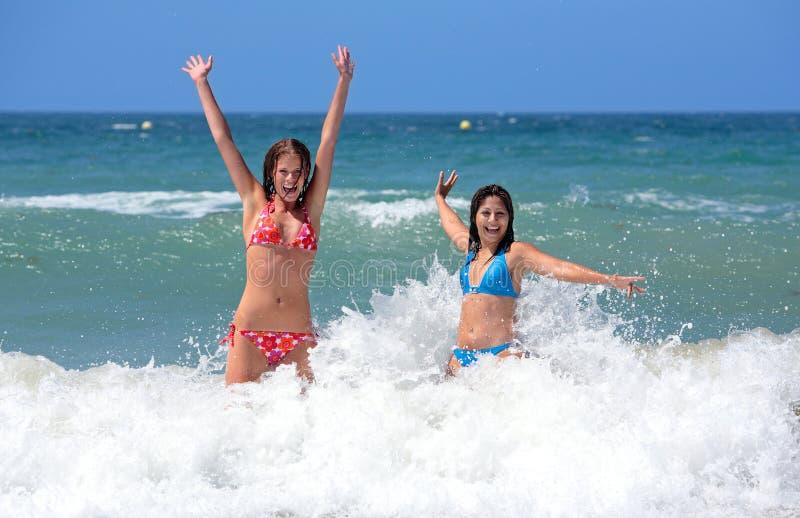 Zwei attraktive junge Freundinnen, die im Meer auf Ferien spielen lizenzfreies stockfoto
