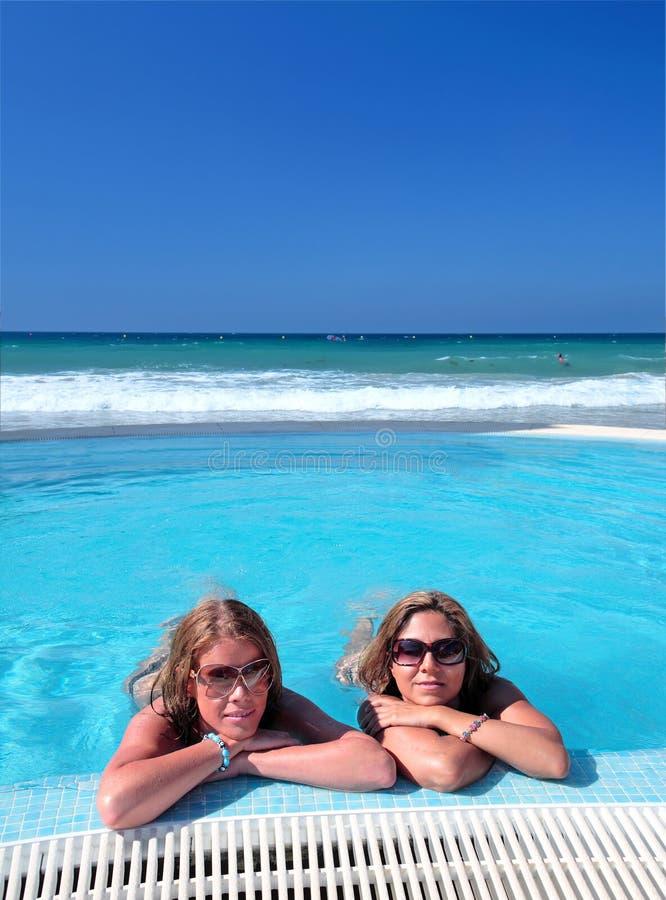 Zwei attraktive junge Mädchen in einem Swimmingpool auf dem Strand stockbilder