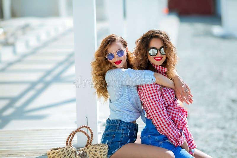 Zwei attraktive Mädchen, nette beste Freunde, die Spaß am Strandfest haben Tragende Sommerausstattung, -kurze Hosen und -t-Shirts lizenzfreie stockfotos