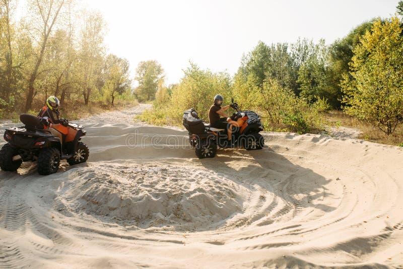 Zwei atv Reiter in den Sturzhelmen, die Schöße auf Sand laufen lassen lizenzfreie stockfotos