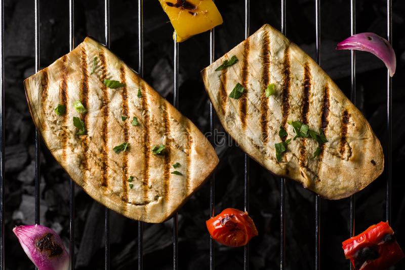 Zwei Auberginen-Scheiben, die auf Holzkohlen-Grill kochen stockfotos